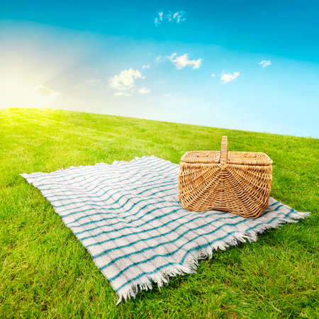 Picnic blanket and basket in a sunlit grassy meadow photo