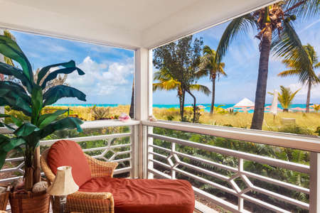 screened: Comfortable chair in the corner of a screened porch overlooking the dunes and Grace Bay Beach, Turks and Caicos