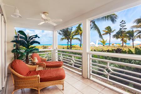 turks: Tumbonas y sillas en un gran porche con vistas a las dunas y playa de Grace Bay, Islas Turcas y Caicos Foto de archivo
