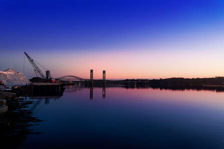 Pre-sunrise light over the Piscataqua River, bridges to Kittery, Maine,  and the huge salt pile  for winter de-icing , Portsmouth, New Hampshire photo