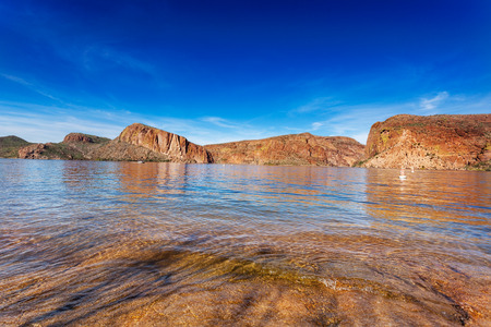 The red cliffs surrounding Canyon Lake, reflected in the calm waters on a sunny Winter afternoon photo