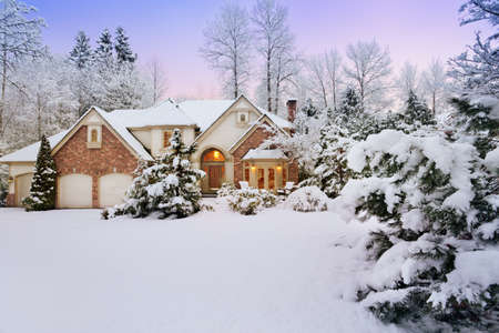 Light fades as night falls on a snowy suburban home photo