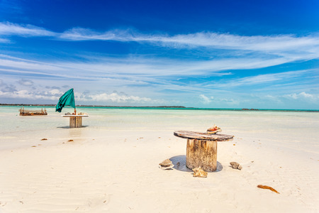 Abandoned cable drum tables on white sand beach near Five Cays, Providenciales, Turks and Caicos photo