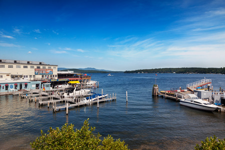 Weirs Beach, Laconia, NH, Aug 19, 2013. Anthonys Restaurant on the Winnipesaukee Pier overlooks the departing floating post office Sophie C on a sunny summer afternoon on Lake Winnipesaukee, New Hampshire