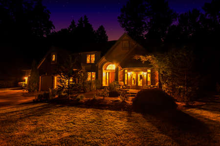 Suburban home at night with windows lit up and light spilling out onto the front lawn photo