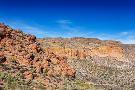 tonto national forest: The Apache Trail through the Tonto National Forest has cliffs, saguaro and boulder-strewn hillsides lining the road. The yellow-green areas are lichen growing on the rock face Stock Photo