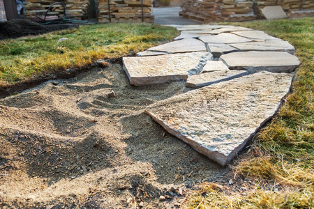 pavers: Stone path beginning with piles of pavers in the background Stock Photo