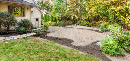 rennovation: Patio area marked out with topsoil placed on flower bed areas and stone retaining wall built around the far edge
