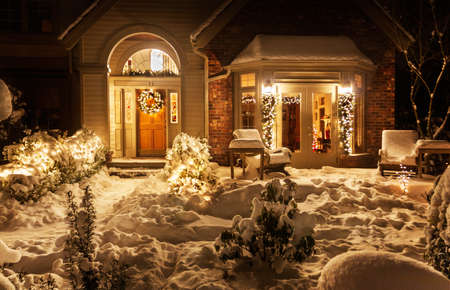 suburban home: Outside lights brighten the snowy entrance to suburban home decorated for Christmas