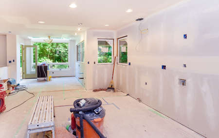 plaster board: Kitchen drywall taped and mud applied to seams. Windows in place and debris cleaned up at the end of the work day Stock Photo