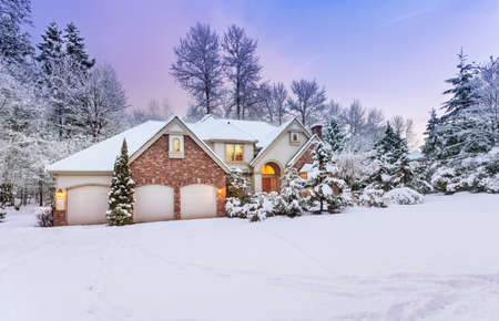 suburban home: Daylight fades over a snow-covered suburban home Stock Photo