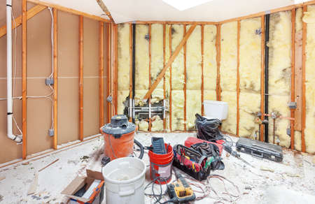 demolishing: Tools for demolishing and cleaning up the debris from a master bathroom to be remodeled. Walls torn back to studs Stock Photo