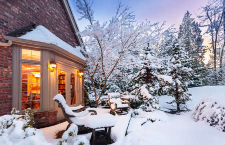 blanketed: Home blanketed in snow as sun goes down on a winter evening