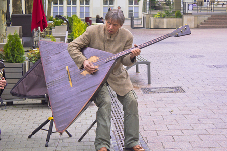 Ville de Luxembourg, Luxembourg - May, 15 2011 A man playing a balalaika in a Luxembourg square. Balalaika is a russian musical instrument, similar like a guitar.