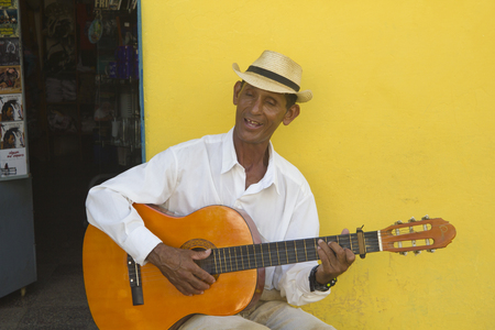 A man is playing the acoustic guitar and sings in a street of Trinidad, Cuba. He wears a white shirt and a hat and is seated in front of a yellow wall Editorial