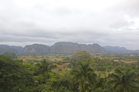 Village at the foot of the mountains in the valley of Vinales in Cuba. Farmers huts and arable fields. Green palm trees and mogot mountain in the Vinales valley. Stock Photo