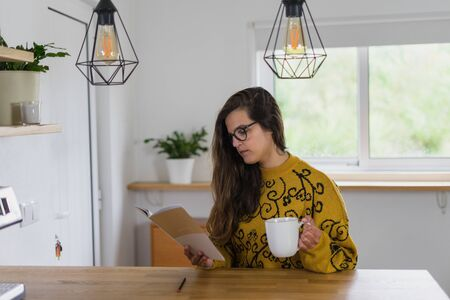 Woman with glasses holding a mug and reading from a notebook on a wooden workbench inside a house. 写真素材