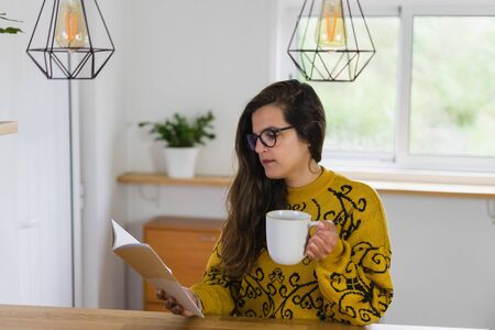 Woman with glasses holding a mug and reading from a notebook on a wooden workbench inside a house. Stockfoto