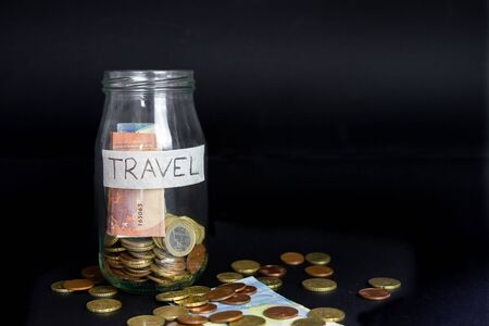 Glass transparent jar labeled handwritten travel. Euro Banknotes and coins inside and outside of the jar. Isolated black background.
