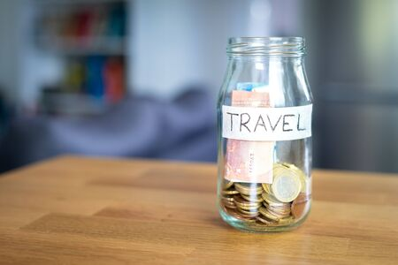 Transparent glass jar labeled travel with euro money in it. Background out of focus. Bokeh