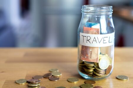 Transparent glass jar labeled travel with euro money in it and outside on top of the wooden table. Background out of focus. Bokeh
