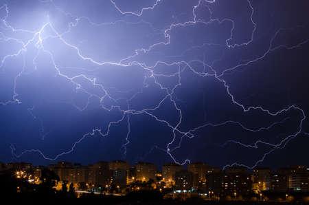 Lightning during thunderstorm in urban area at night