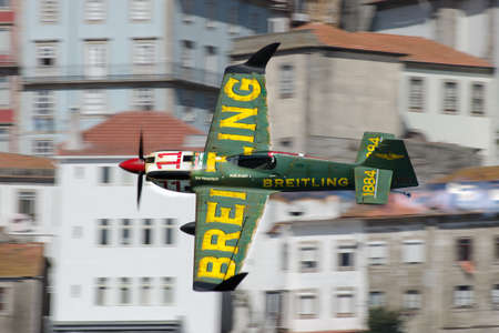 Red Bull Air Race 2017 Porto - Mikael Brageot Breitling flying against buildings background Stock Photo - 86020709