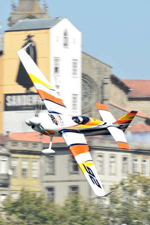 Red Bull Air Race 2017 Porto - Juan Velarde plane flying against historic buildings background Editorial