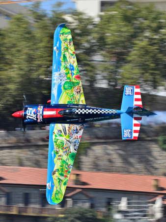Red Bull Air Race 2017 Porto - Petr Kopfstein plane flying vertical against buildings background