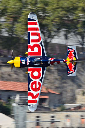 Red Bull Air Race 2017 Porto - Martin Sonka plane flying vertical against buildings background Editorial