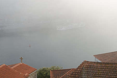 Foggy day over tile roofs on Douro river in Porto, Portugal