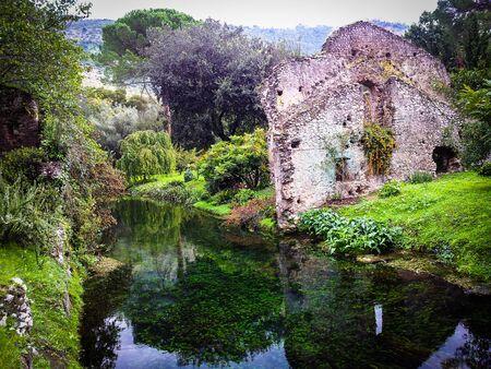 Ruins and refection in Giardini di Ninfa in Italy