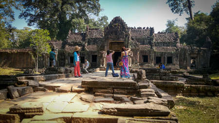 Curious group of tourists in the temple Preah Khan in in Angkor Wat. Ancient Khmer architecture near Siem Reap, Cambodia Редакционное