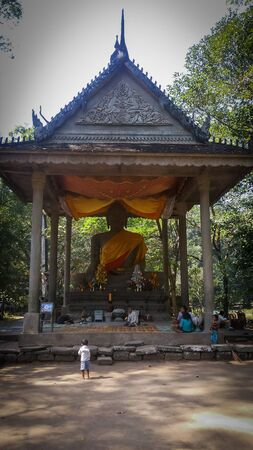 Great Buddha statue with yellow and orande clothes with family begging donates at the bottom in Angkor Wat, Cambodia