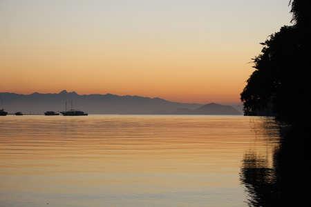 Boats silhouette at sunrise sunset in Canal de Bertioga, Sao Paulo, Brazil. Orange and black colors