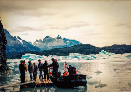samall group of tourists leaving a boat at Glacier Grey at Torres del Paine, Chile
