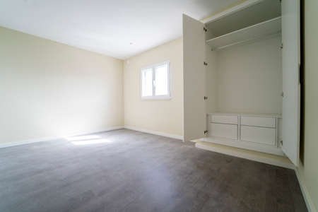 Empty room with dark wooden floating laminate flooring and wardrobe. House interior, wide bedroom space. Newly recently painted new apartment or house. Wood floor. Real state and property management Stockfoto