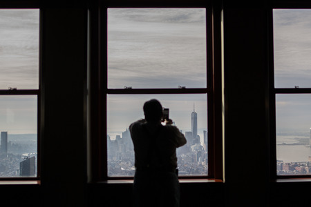 A man taking a picture of Lower Manhattan, New York, from The Empire State Building, a touristic point visited by thousands of people every day.