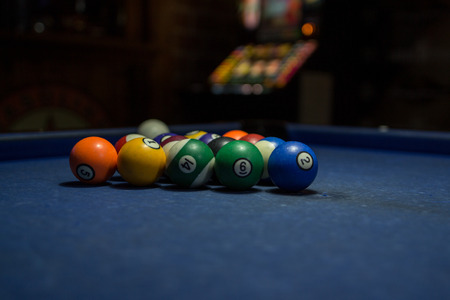 Pool balls over a blue table prepared for the game in a bar.