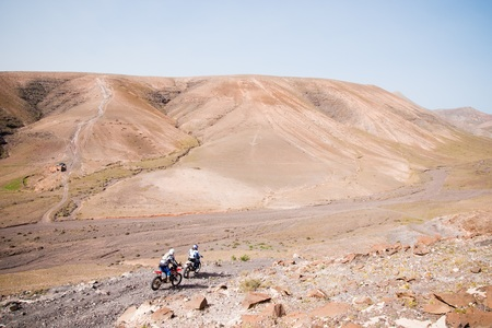 Motorcyclists driving through a stony track of some desert mountains living their travel adventure