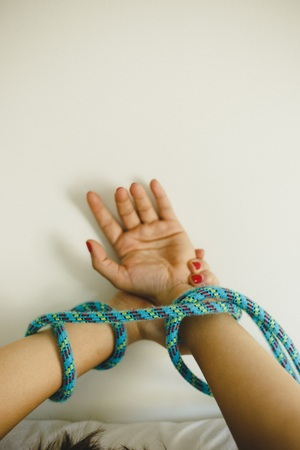 Hands of sexy and young woman tied with ropes to the bed