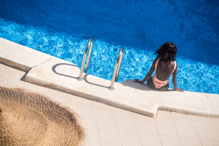 Young black woman sunbathing on the edge of a pool with cool blue water cooling off.