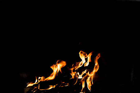 Flames in the fire of a red and yellow barbecue.