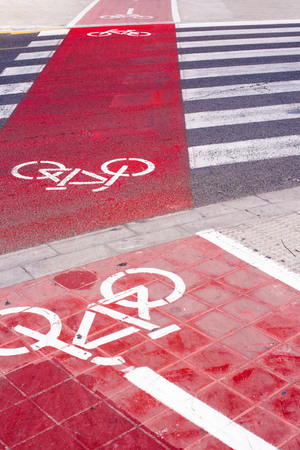 Signs and bike lane markings painted on the asphalt of the streets of an urban city