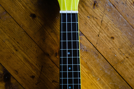 Small yellow ukulele on wooden floor ready to be played