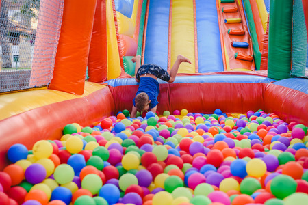 Inflatable castle full of colored balls for children to jump Stock Photo