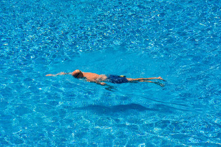 Man swimming in a pool in summer