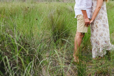Enamored couple walking through tall grasses holding hands.