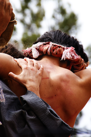 Religious representation by two people of the passion of Christ, man whipped with wounds