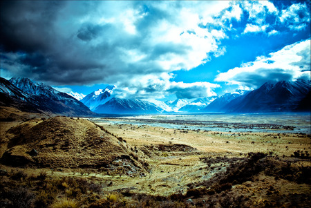 Snowy mountainous landscape of the New Zealand alps with dramatic skies, during a motorhome trip. Stock Photo